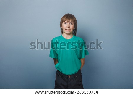 Boy teenager twelve years in a green T-shirt  showing teeth surprise - stock photo