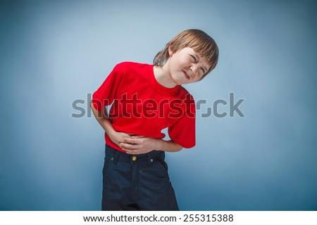 Boy teenager twelve years in  red shirt abdominal pain, gastritis, diarrhea - stock photo