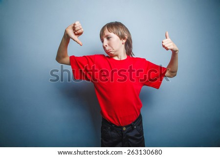 Boy, teenager, twelve years in  red shirt showing sign of Yes - stock photo