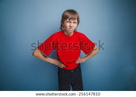 Boy, teenager, twelve years in the red shirt, hands in the side, angry - stock photo