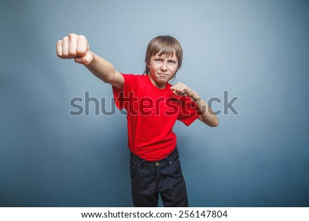 Boy, teenager, twelve years  red  in shirt, red showing  fists his - stock photo