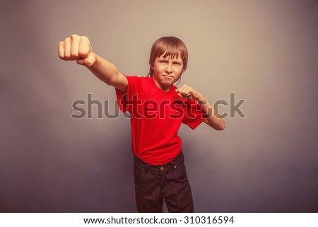 Boy, teenager, twelve years  red  in shirt, red showing  fists his retro - stock photo