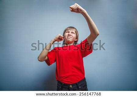 Boy, teenager, twelve years  red  in shirt, showing  fists his - stock photo