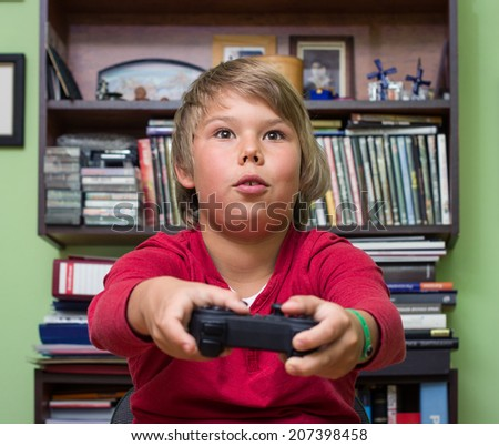 Boy teenager with remote control in hand playing a video game console. - stock photo
