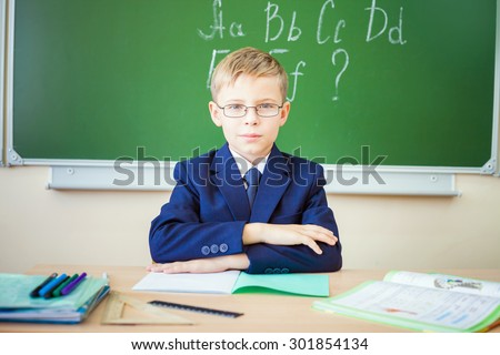 Boy thinking and sits at a desk at school with glasses. Against the background of the school board english alphabet. Schoolboy dressed in a school uniform. - stock photo