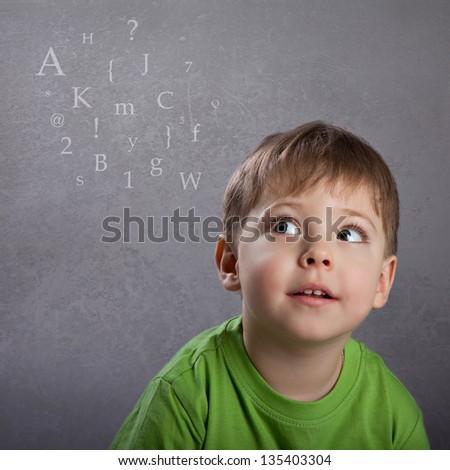 Boy thinking on grey grunge background - stock photo