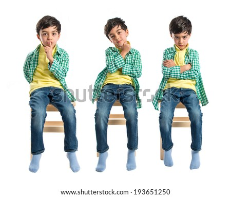 Boy thinking on wooden chair over white background - stock photo