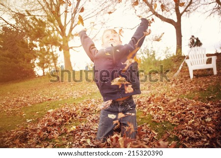 Boy throwing autumn leaves - stock photo