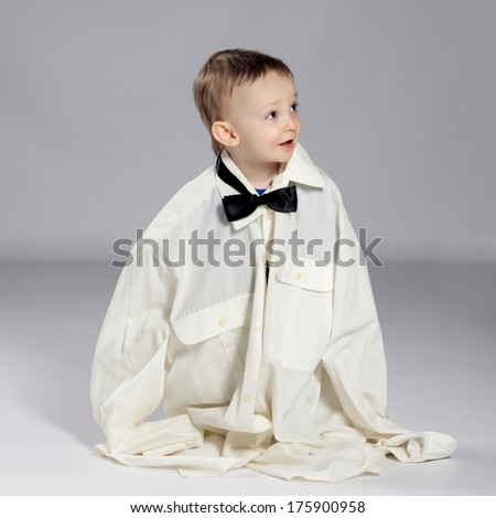 Boy toddler businessman, standing dressed in grown-shirt with bow tie