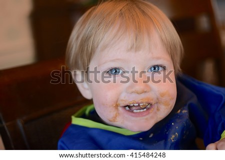 boy toddler eating peanut butter with messy face