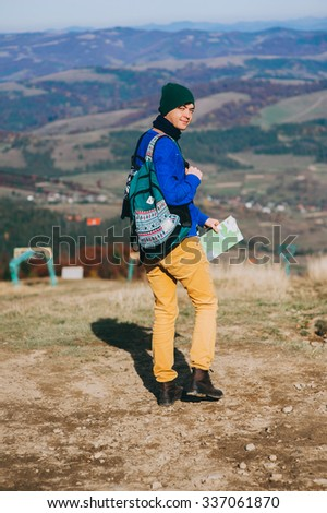 boy tourist in mountains with map