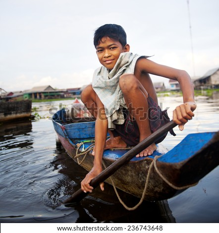 Boy traveling by boat in floating village. - stock photo