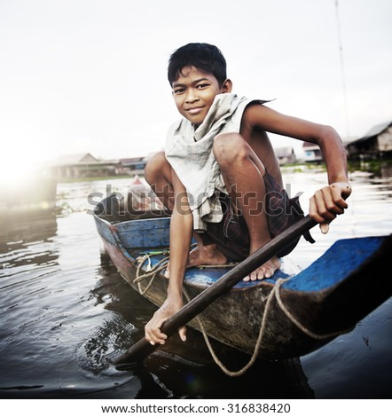 Boy Traveling by Boat in Floating Village Concept - stock photo
