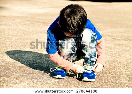 Boy trying to tie his shoes by himself alone on the concrete road. - stock photo