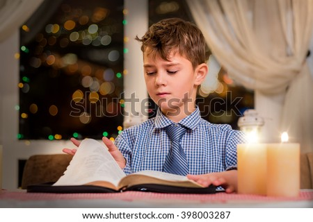 Boy turning page of book. Child and book by candlelight. He read half of it. Huge collection of poems.