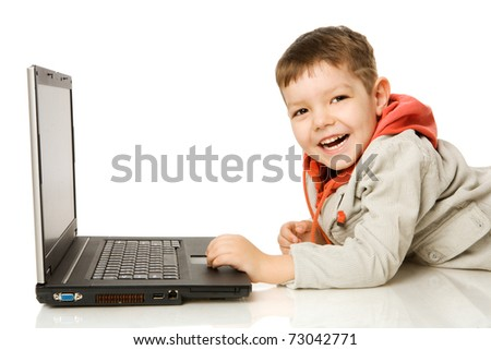 Boy typing on laptop and laughing isolated on white - stock photo