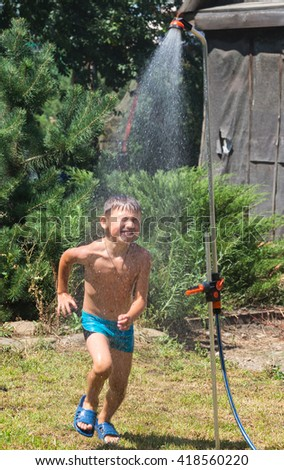 Boy under a shower in the hot day - stock photo