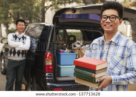 Boy unpacking car for college - stock photo