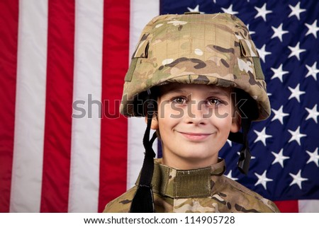 Boy USA soldier in front of American flag. Young boy dressed like a soldier