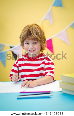 Boy using a pencil to write on paper at the desk - stock photo