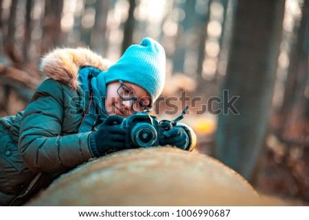 Boy using digital camera taking photo in the nature, hobbies concept