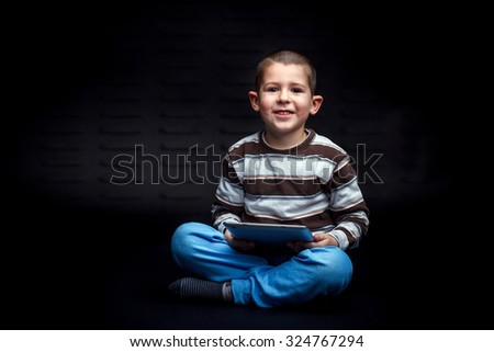 Boy using digital tablet on black background - stock photo