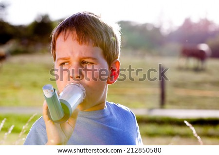 Boy using inhaler for asthma in village with cows and sunset - stock photo