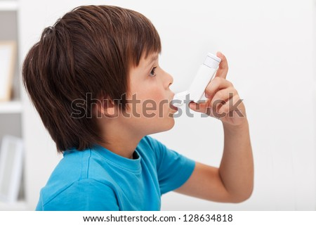 Boy using inhaler - respiratory system illness - stock photo