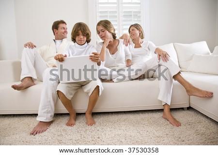 Boy using laptop sitting with family on white sofa - stock photo