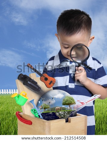 Boy using magnifying glass with toys and globe burst from wooden box. (Elements of this image furnished by NASA) - stock photo