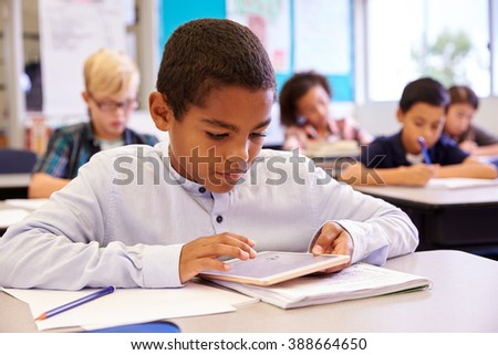 Boy using tablet computer in elementary school class - stock photo