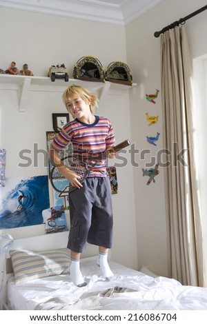 Boy (6-8) using tennis racquet as guitar, jumping on bed - stock photo