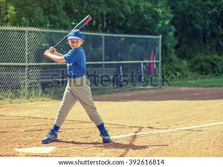 Boy waiting for the ball in a baseball game with cross processed filter - stock photo
