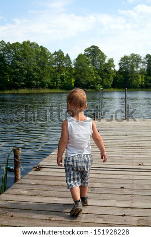 boy walking on pier - stock photo