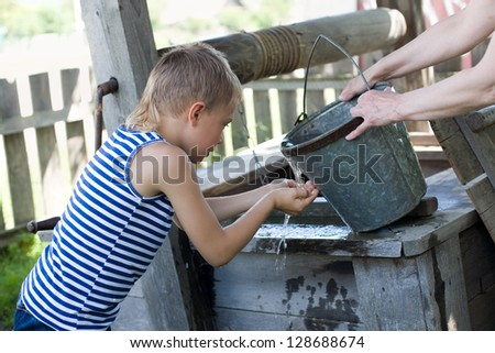 Boy washes his face with water from a well on a hot day. Russia. - stock photo
