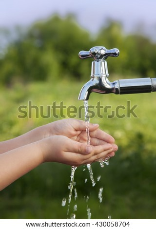 boy washes his hand under the faucet in the garden - stock photo