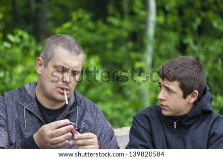 Boy watching how father ignited a cigarette