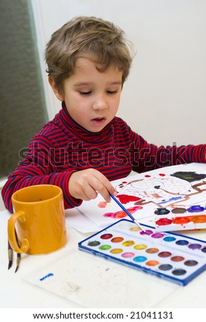 Boy watercolors paints on a sheet of paper