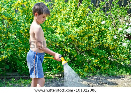 Boy watering plants in the garden with a hose with a sprayer - stock photo