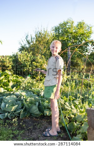 Boy watering the garden with hose - stock photo
