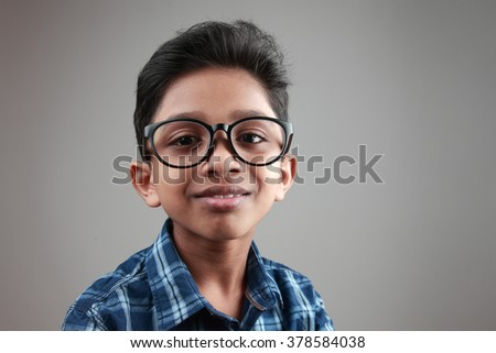 Boy wearing a big spectacle with a smiling expression - stock photo