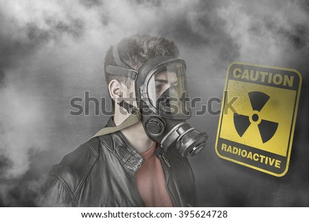 Boy wearing a gas mask against nuclear warning sign - stock photo