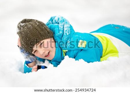Boy wearing a hut lies on snow - stock photo