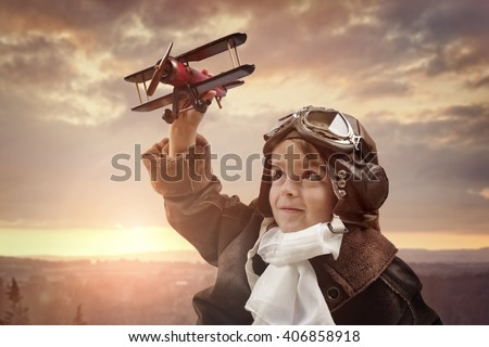 Boy wearing old-fashioned aviator hat, scarf and goggles holding a wooden biplane up in the air with sunset - stock photo