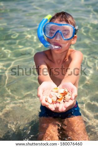 Boy wearing snorkeling gear showing seashells - stock photo
