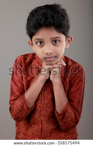 Boy wearing traditional Indian dress with a focussed look - stock photo