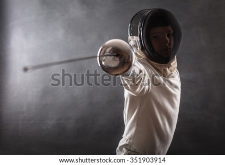 Boy wearing white fencing costume and black fencing mask standing with the sword practicing in fencing. - stock photo