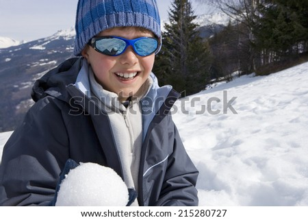 Boy wearing woolen hat and sunglasses in snow field, holding snow ball, smiling, portrait