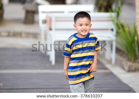 boy wearing yellow striped shirt and smiling