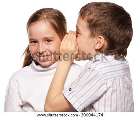 Boy whispers girl in the ear secret. Childrens gossip - stock photo